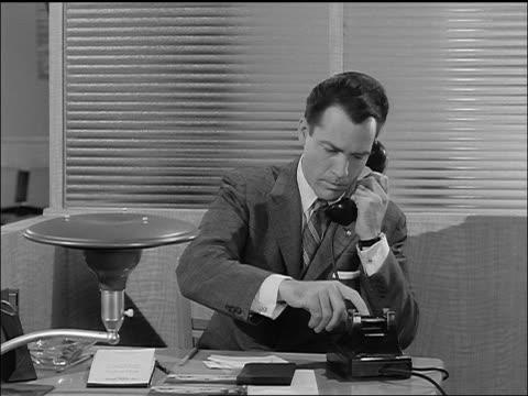 vídeos de stock, filmes e b-roll de b/w 1957 businessman (carl betz) making phone calls in office - 1957
