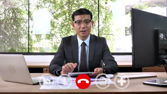 vidéos et rushes de businessman manager connecté chat vidéo en ligne parler au personnel - costume habillé