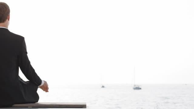 stockvideo's en b-roll-footage met hd dolly: businessman meditating by the sea - in kleermakerszit