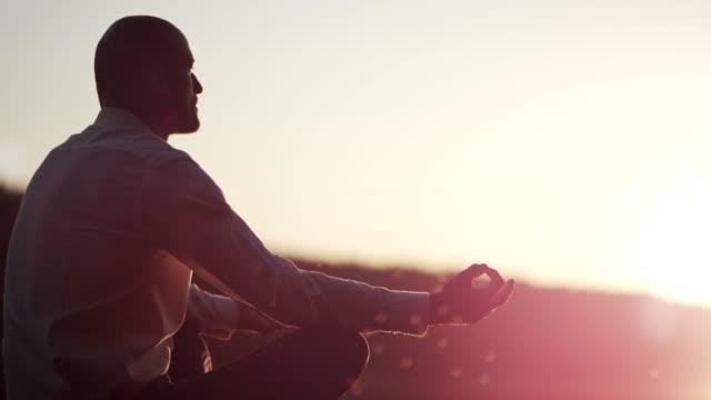 vídeos de stock e filmes b-roll de businessman meditating on lake pier. sunset - zen