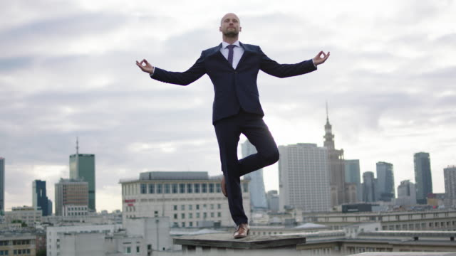 geschäftsmann am dach zu meditieren. - junger mann allein stock-videos und b-roll-filmmaterial