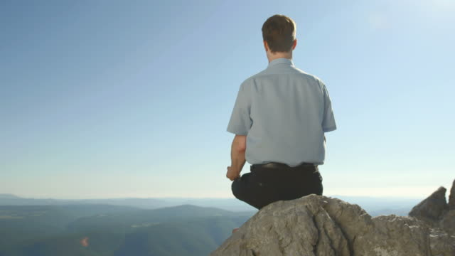 HD DOLLY: Businessman Meditating On The Cliff