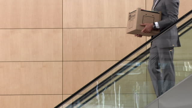 slo mo ms businessman moving down escalator, carrying box of office items, cape town, south africa - 2009年点の映像素材/bロール