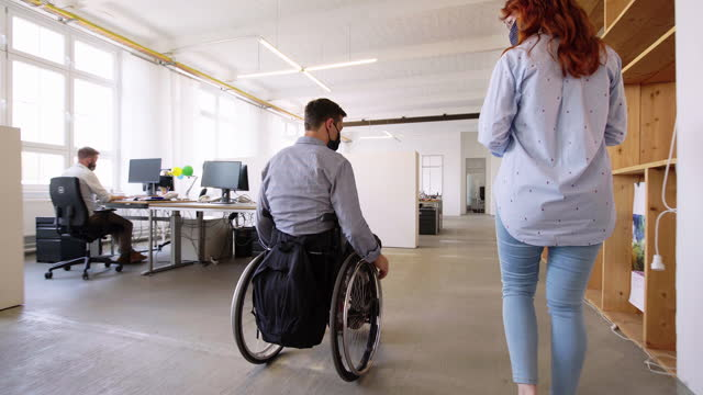 businessman moving in office on wheelchair with female colleague - working stock videos & royalty-free footage
