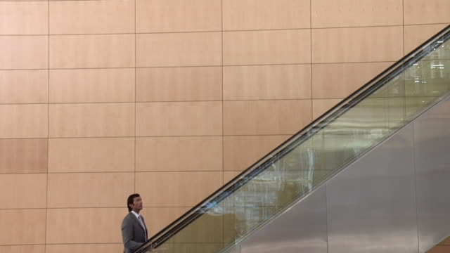 SLO MO WS Businessman moving up escalator, talking on mobile phone, Cape Town, South Africa