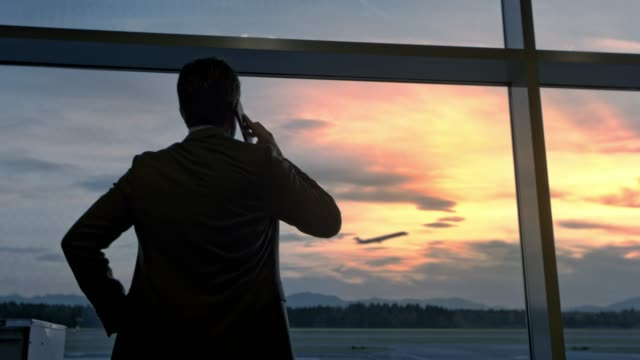 businessman observing the plane take off through the glass wall at the airport while talking on the phone - gate stock videos & royalty-free footage