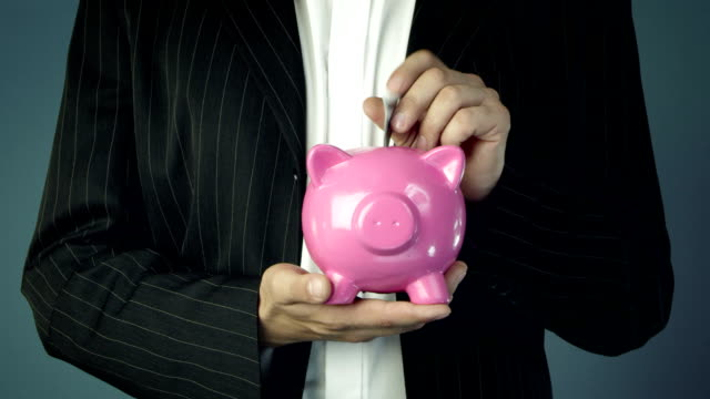 stockvideo's en b-roll-footage met businessman offering a pink piggy bank - investering