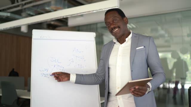 uomo d'affari in una presentazione online, riunione video - punto di vista della fotocamera - strategia di vendita video stock e b–roll