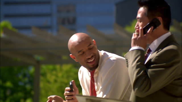 businessman on break outside talking on mobile phone while co-worker stands nearby - giacca e cravatta video stock e b–roll