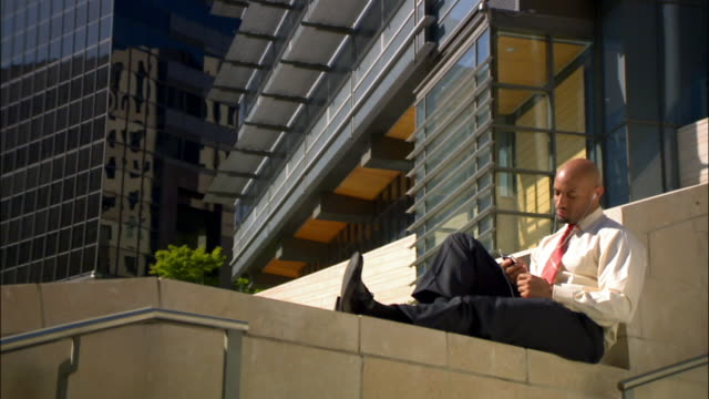 Businessman on break sitting on ledge and listening to MP3 player