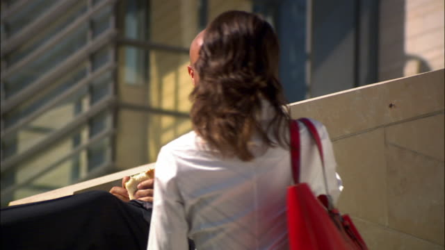 businessman on break sitting on ledge eating lunch / has conversation with businesswoman walking past - hemd und krawatte stock-videos und b-roll-filmmaterial