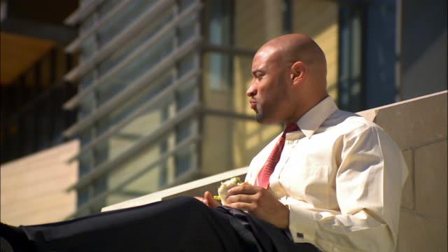 stockvideo's en b-roll-footage met businessman on break sitting on ledge eating lunch - overhemd en stropdas