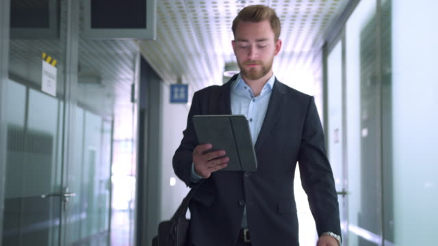 businessman on her digital tablet on hallway - place of work stock videos & royalty-free footage