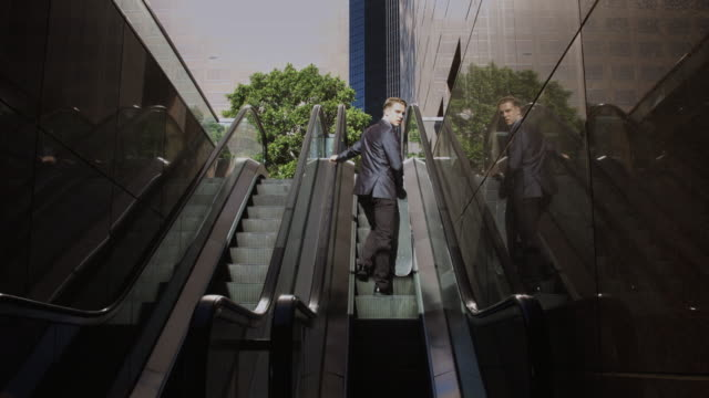 vídeos de stock e filmes b-roll de businessman on outdoor escalator - com sombra