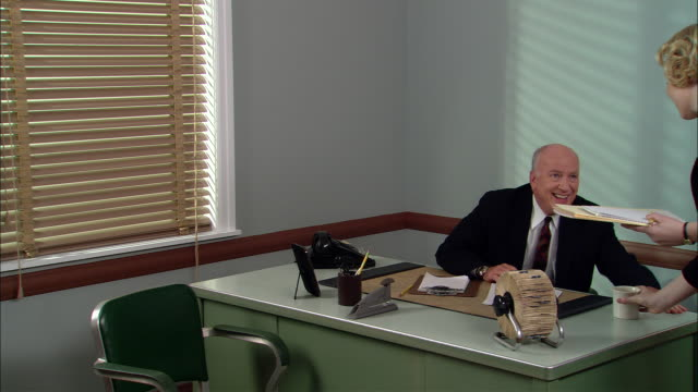 ms  businessman on phone in office/ secretary arriving and sitting down/ boss making inappropriate comment/ secretary getting up and walking out of his office/ new york city - 性的嫌がらせ点の映像素材/bロール