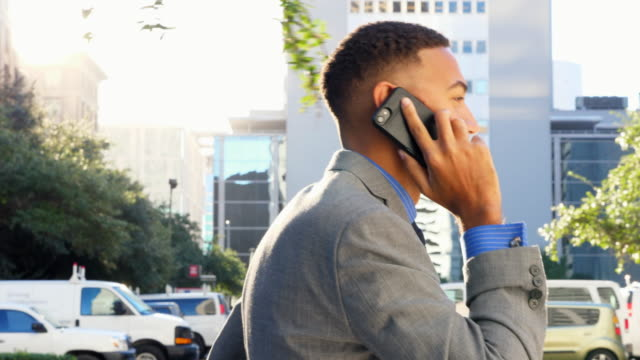 TS Businessman on phone while walking on city sidewalk