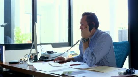 ms businessman on phone while working on computer in office - skrivbord bildbanksvideor och videomaterial från bakom kulisserna