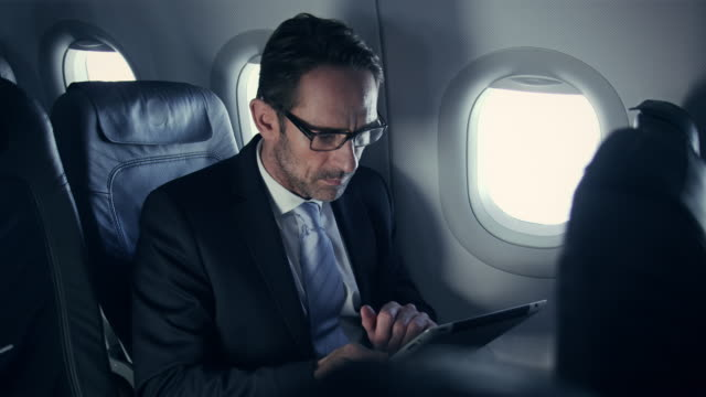 stockvideo's en b-roll-footage met businessman on plane - zakenreis