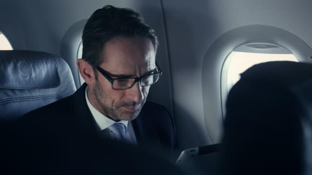 vidéos et rushes de homme d'affaires sur un avion - voyage d'affaires