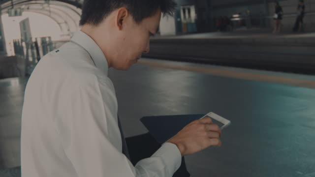 実業家のタブレットで駅 - 鉄道のプラットホーム点の映像素材/bロール