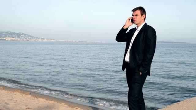 Businessman on the phone at beach
