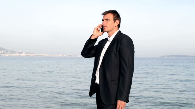 businessman on the phone at the beach - short phrase stock videos & royalty-free footage