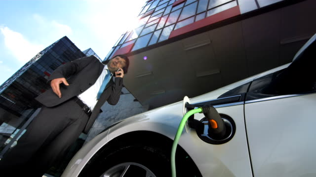 HD: Businessman On The Phone Charging His Car