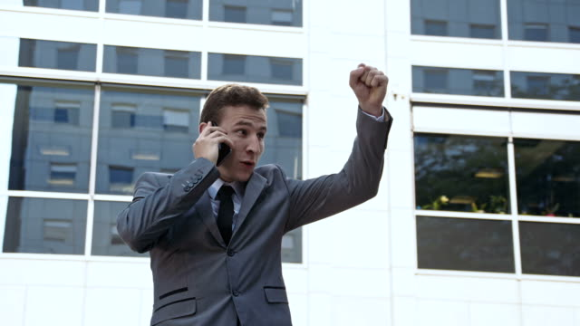 slo mo businessman on the phone showing a fist pump - punching the air stock videos & royalty-free footage
