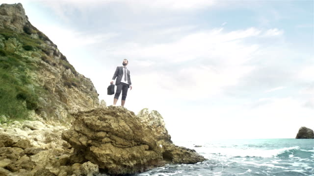 businessman on the rocky coastline - 4k resolution - arts culture and entertainment stock videos & royalty-free footage