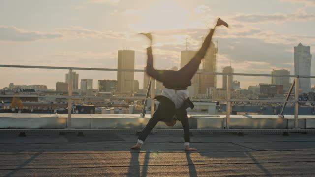 vidéos et rushes de homme d'affaires sur le toit. debout sur les mains - jour