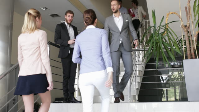 Businessman on the stairs using smart phone while his colleagues passing by