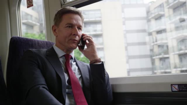 Businessman on train on his commute talking on smart phone