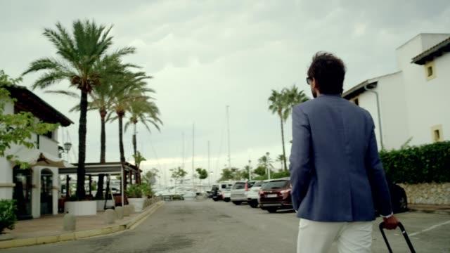 vidéos et rushes de homme d'affaires, en vacances. pied avec valise sur marina - suivre activité avec mouvement