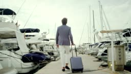 Businessman on vacation. Walking with suitcase on marina