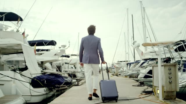 vídeos de stock e filmes b-roll de businessman on vacation. walking with suitcase on marina - veículo aquático