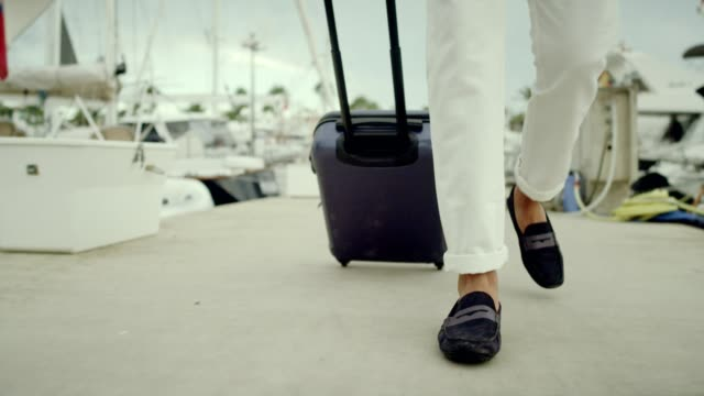 businessman on vacation. walking with suitcase on marina - yachting stock videos & royalty-free footage