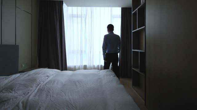 vidéos et rushes de rideaux ouverts d'homme d'affaires dans la chambre d'hôtel - un seul homme d'âge moyen