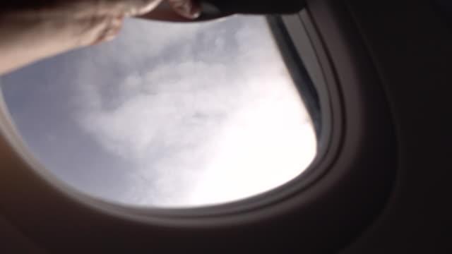 geschäftsmann öffnet flugzeugfenster - flugpassagier stock-videos und b-roll-filmmaterial
