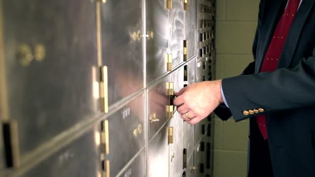 businessman opening safety deposit box - documento video stock e b–roll
