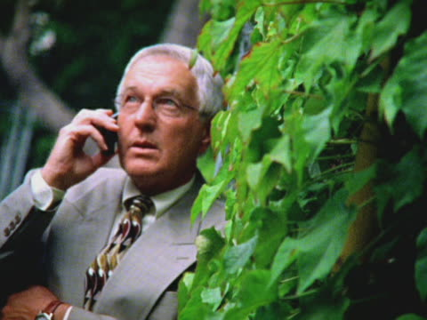 businessman outdoors on mobile phone - kompletter anzug stock-videos und b-roll-filmmaterial