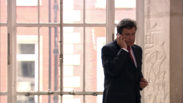 ms businessman pacing in hallway while talking on mobile phone/ second businessman approaching and greeting him/ men walking off together/ london  - hanging up stock videos & royalty-free footage
