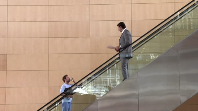 slo mo ws businessman passing by young man in pajamas moving up escalator, yawning and drinking coffee, cape town, south africa - refreshment stock videos & royalty-free footage