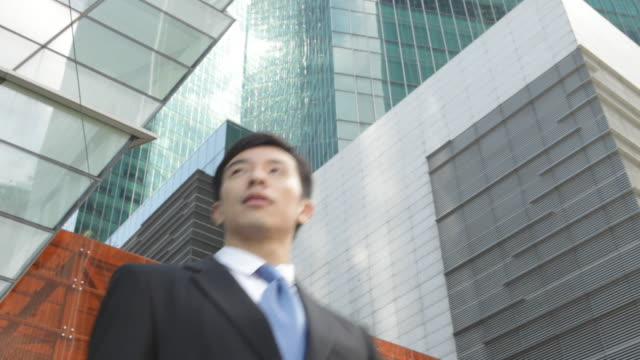 A businessman pauses in front of modern office buildings.
