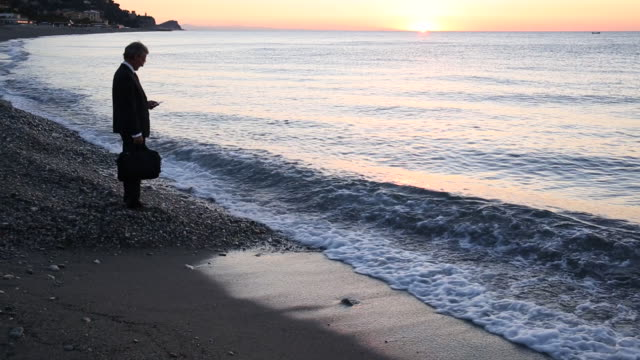 vidéos et rushes de businessman pauses with smart phone at beach, looks over sea - costume complet