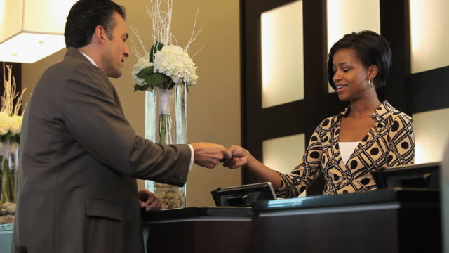 MS Businessman paying bill with credit card at hotel lobby / Richmond, Virginia, USA