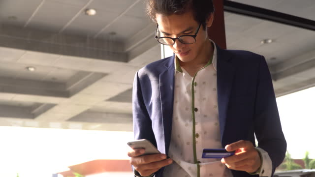vídeos de stock, filmes e b-roll de empresário, pagar contas e usando serviços bancários online no telemóvel - compra online