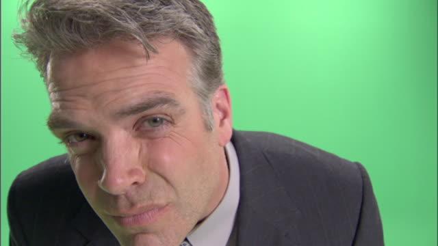 ecu, businessman peeking into camera in studio - peeking stock videos & royalty-free footage