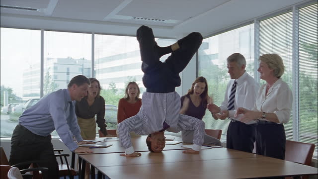 A businessman performs a headstand on a table, then moves to his feet.