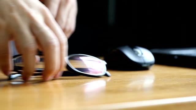 vidéos et rushes de homme d'affaires chercher une paire de lunettes à porter pour le travail. - soulever