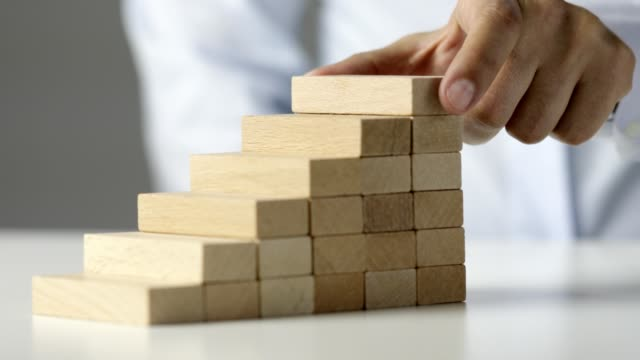 商人放置最後一個木塊完成樓梯,顯示增長和改進 - 帶 握住 個影片檔及 b 捲影像